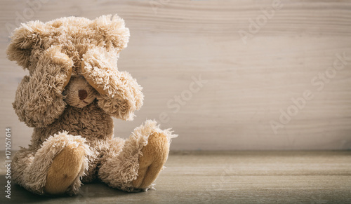 Child abuse concept. Teddy bear covering eyes