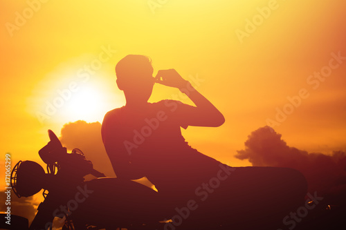 Keuken foto achterwand Ontspanning Silhouette of man and a motorcycle with sunset background.