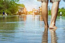 Young Man Walks Through The Flood With His Bare Feet.