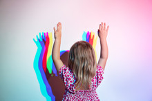 Little Girl Stands Against The Wall With Her Arms Raised With Her Back To The Camera. On The Wall Is A Diffraction Shadow
