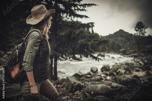 Fototapeta Beautiful woman hiker near wild mountain river.