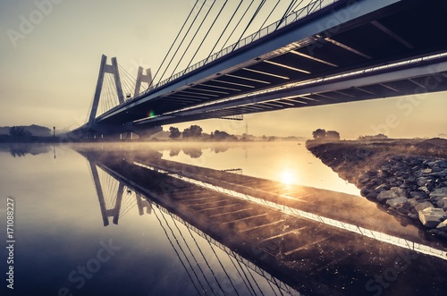 Fotobehang Brug Cable stayed bridge, Krakow, Poland, in the morning fog over Vistula river