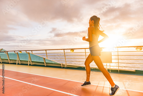 8e60171af77 Fit woman jogging at sunset on run lanes on deck of cruise ship during  summer holidays. Active healthy ... See More
