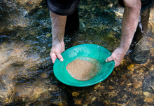 Gold Pan Filled With Mineral Rich Material Ready To Be Panned. Prospecting For Gold And Gemstones. Fun And Adventure Enjoying Recreational Outdoor Activity.