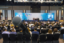 Microphone With Abstract Blurred Photo Of Conference Hall Or Meeting Room With Attendee Background, Business And Education Concept
