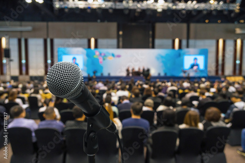 Fotografía  Microphone with Abstract blurred photo of conference hall or meeting room with a