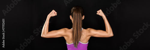 Foto  Strong fitness woman showing back and biceps muscles strength