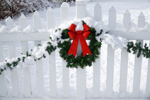 Christmas Wreath On The White Fence After Snow