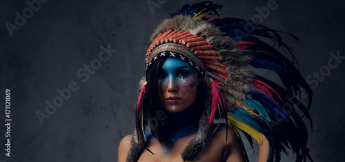Photo Female with Indian feather hat and colorful makeup.