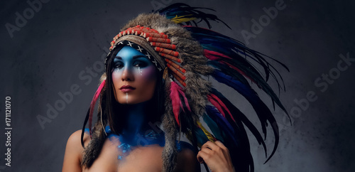 Female with Indian feather hat and colorful makeup  - Buy this stock