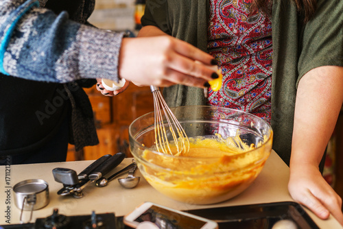 two girls following pumpkin pie recipe for halloween - adding egg yolks to batte Canvas Print