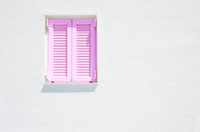 White Wall And Window With Pink Shutters.