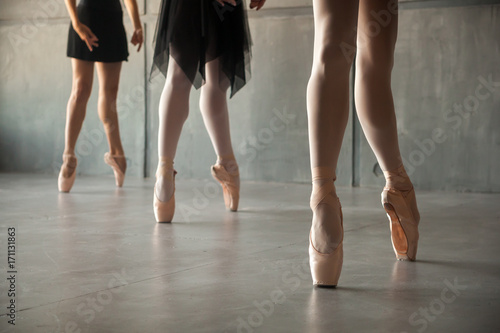 Close-up of the legs of three young  ballerinas in white pantyhose, black packs and pointes performing a dance in a dark studio Fototapeta