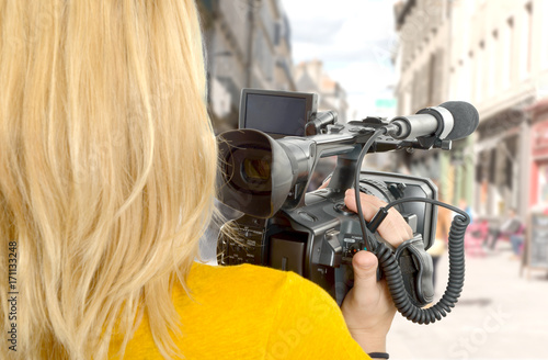 Photo  woman with his professional camcorder in the street