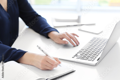 Young woman using laptop for searching information in internet at table