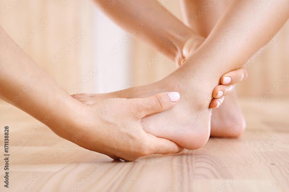 Fototapeta Uraz stopy. Pierwsza pomoc, kobieta sprawdza stopę dziecka