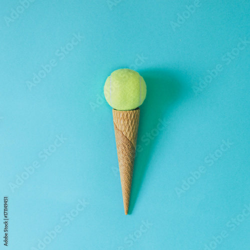 Ice cream cone with tennis ball on bright blue background. Minimal food concept.