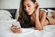 Attractive Asian Woman In Sexy Lingerie Using Mobile Phone