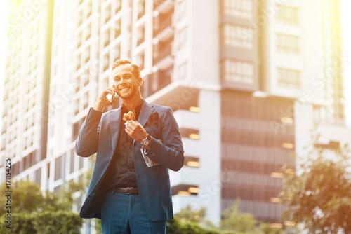 Photo  Low angle of joyful businessman talking on phone outdoors