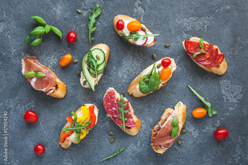 Traditional spanish tapas on dark background. Flat lay, top view