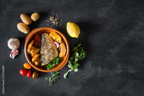 Obraz na plátně Baked dorado with fresh salad and vegetables