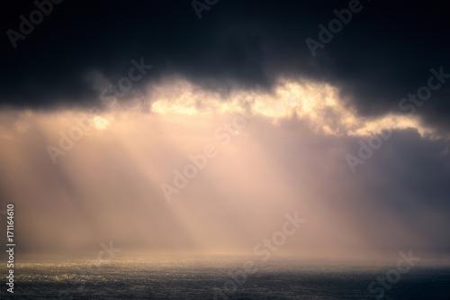 Платно rain on the sea with stormy clouds and sun rays