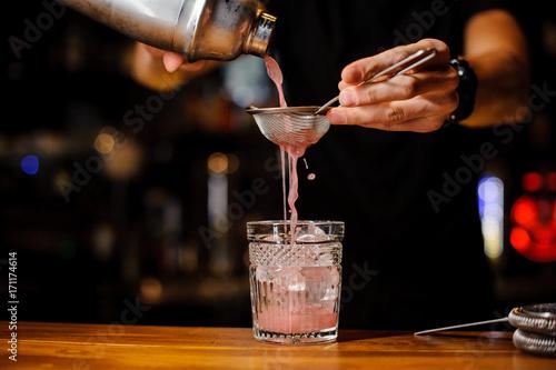 Fotografia  Bartender hand pouring pink cocktail drink in bar
