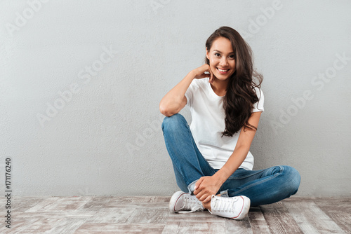 Fotografía  Joyful pretty asian woman sitting on the floor