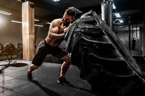 Shirtless man flipping heavy tire at crossfit gym Fototapeta