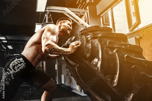 Valokuva Shirtless man flipping heavy tire at crossfit gym