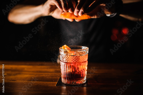 Fotografija bartender with cocktail and orange peel preparing cocktail at bar