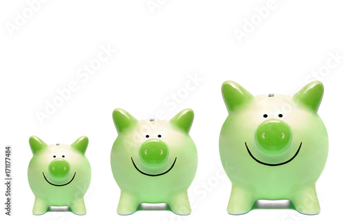 Foto Three green piggy banks in different sizes / Green business and grown concept