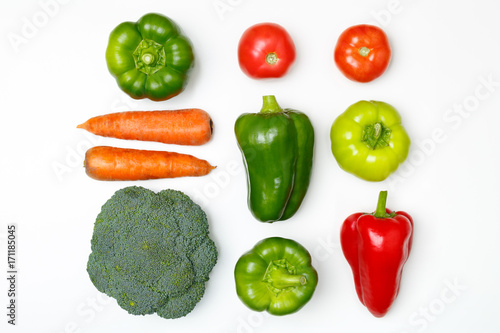 Vegan food. Top view of broccoli, green pepper, tomatoes, red paprika, carrot on a white background.