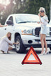 Pretty women having problem with car on the road