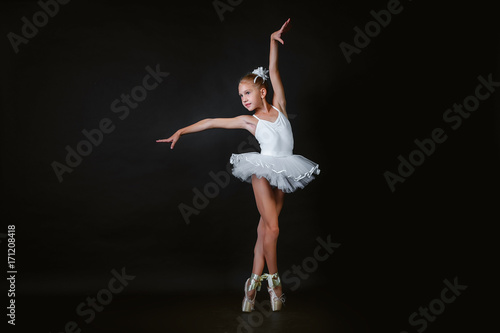 A small young ballerina performs an element of ballet dance on a black background Canvas Print