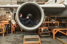 Male Aircraft Maintenance Engineer Fixing Turbine Blade Of