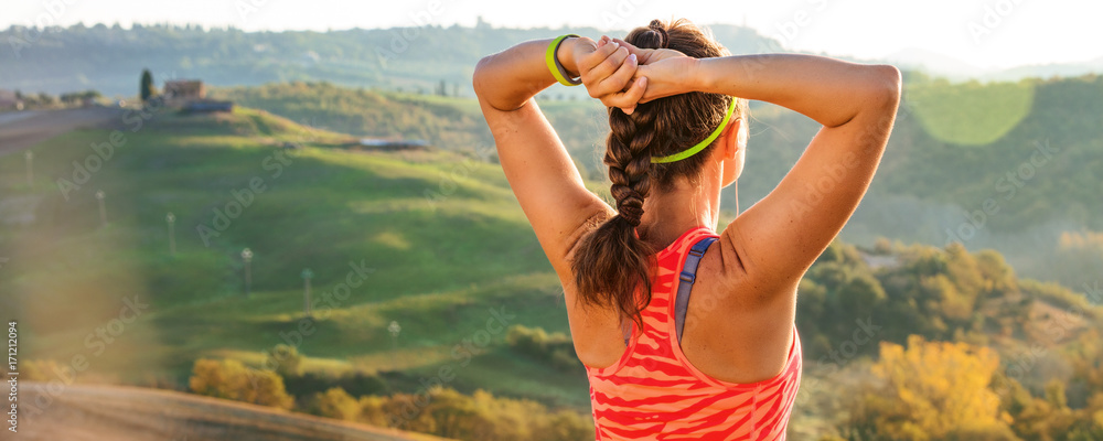 Fototapeta sportswoman against scenery of Tuscany looking into distance