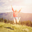 Young teenage girl jumping with raising hands over head in mountains on summer vacation