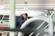 Aircraft maintenance engineer examining turbine engine of