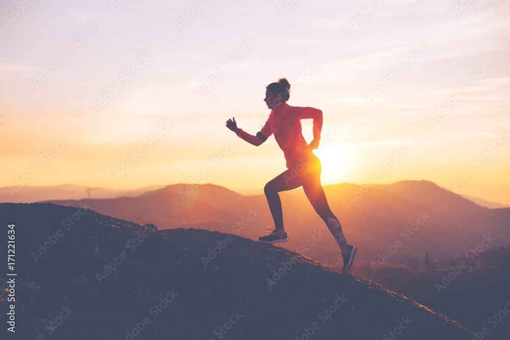 Athletic girl finishes a run in the mountains at sunset. Sport tight clothes. Intentional motion blur.