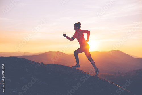 Fototapeta sport athletic-girl-finishes-a-run-in-the-mountains-at-sunset-sport-tight-clothes-intentional-motion-blur