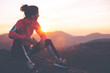 canvas print picture - Athletic woman resting after a hard training in the mountains at sunset. Sport tight clothes.