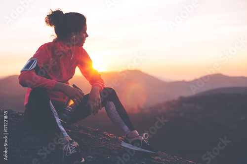 Papiers peints Jogging Athletic woman resting after a hard training in the mountains at sunset. Sport tight clothes.