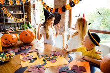 Getting Ready For The Halloween Costume Party, Blond Mother With Two Small Cheerful Kids, Girl Holds The Witch Hat, Boy Gestures Like Sign, Bright Decorated Room, Spooky Design, Bats, Spider Nets