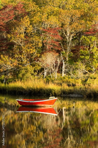 Photo  Red dory moored in still inlet on Cape Cod with autumn trees in background, refl