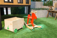 Toy Storage With Wheels And A Red Rocking Horse On The Artificial Grass