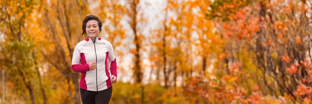 Fototapeta Autumn running middle age Asian woman jogging in park banner panorama. Active lifestyle mature lady in her 50s living a healthy life.