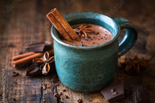 Poster Chocolate Hot chocolate with a cinnamon stick, anise star and grated chocolate topping in festive Christmas setting on dark rustic wooden background