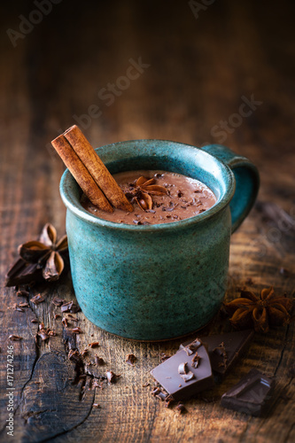 Printed kitchen splashbacks Chocolate Cup of hotchocolate with a cinnamon stick, star anise and grated dark chocolate as a topping on dark rustic wooden background