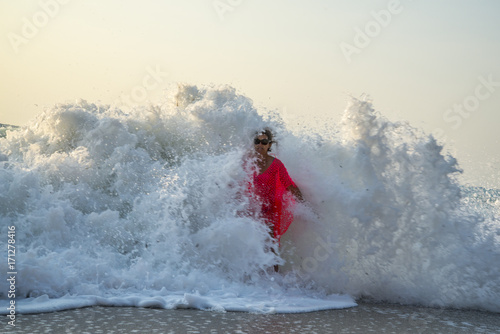 A wave of two meters surprises a young woman on the seashore/ A young woman caug Canvas Print